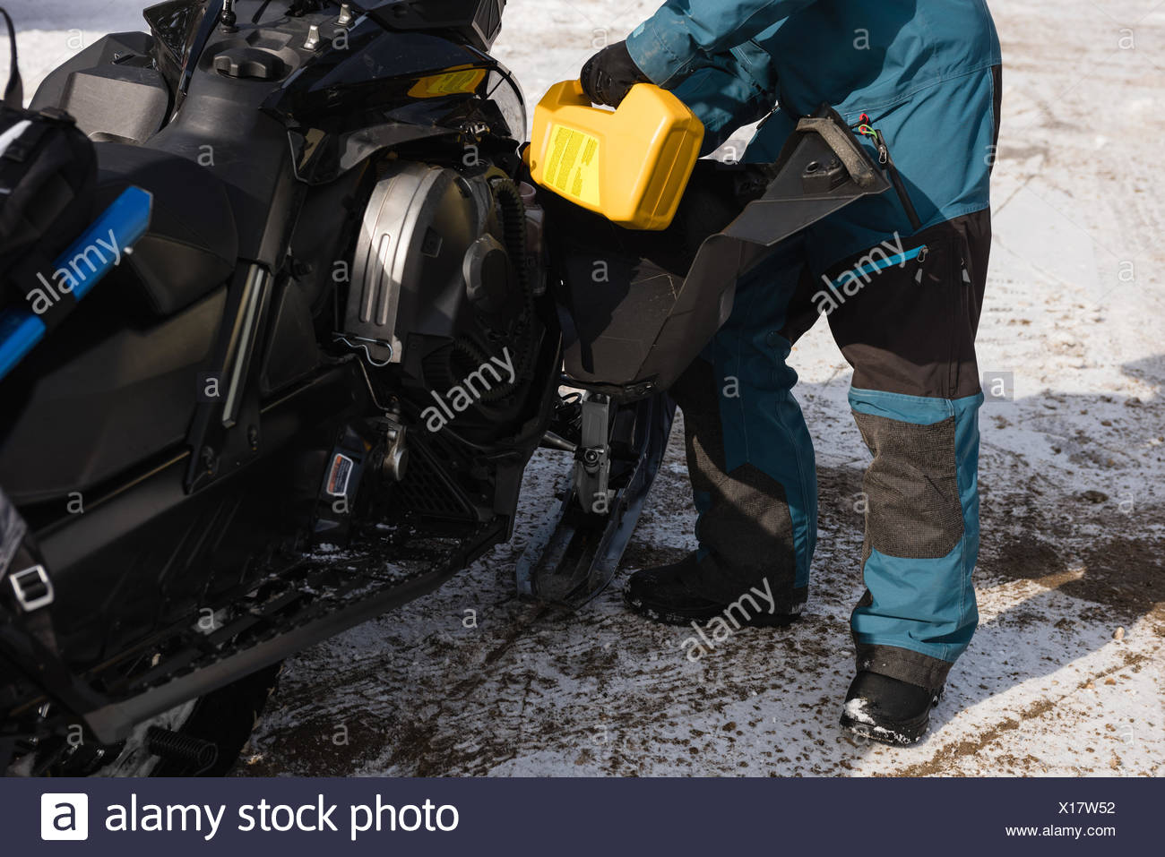 Man filling gas tank of snowmobile during winter - Stock Image
