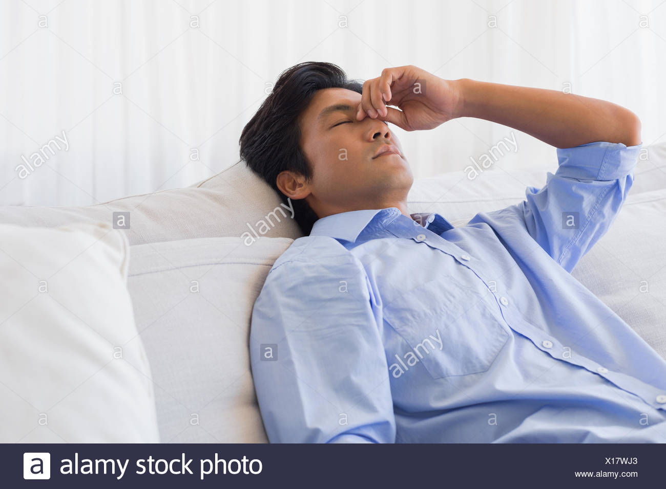 Man sitting on couch with a headache - Stock Image