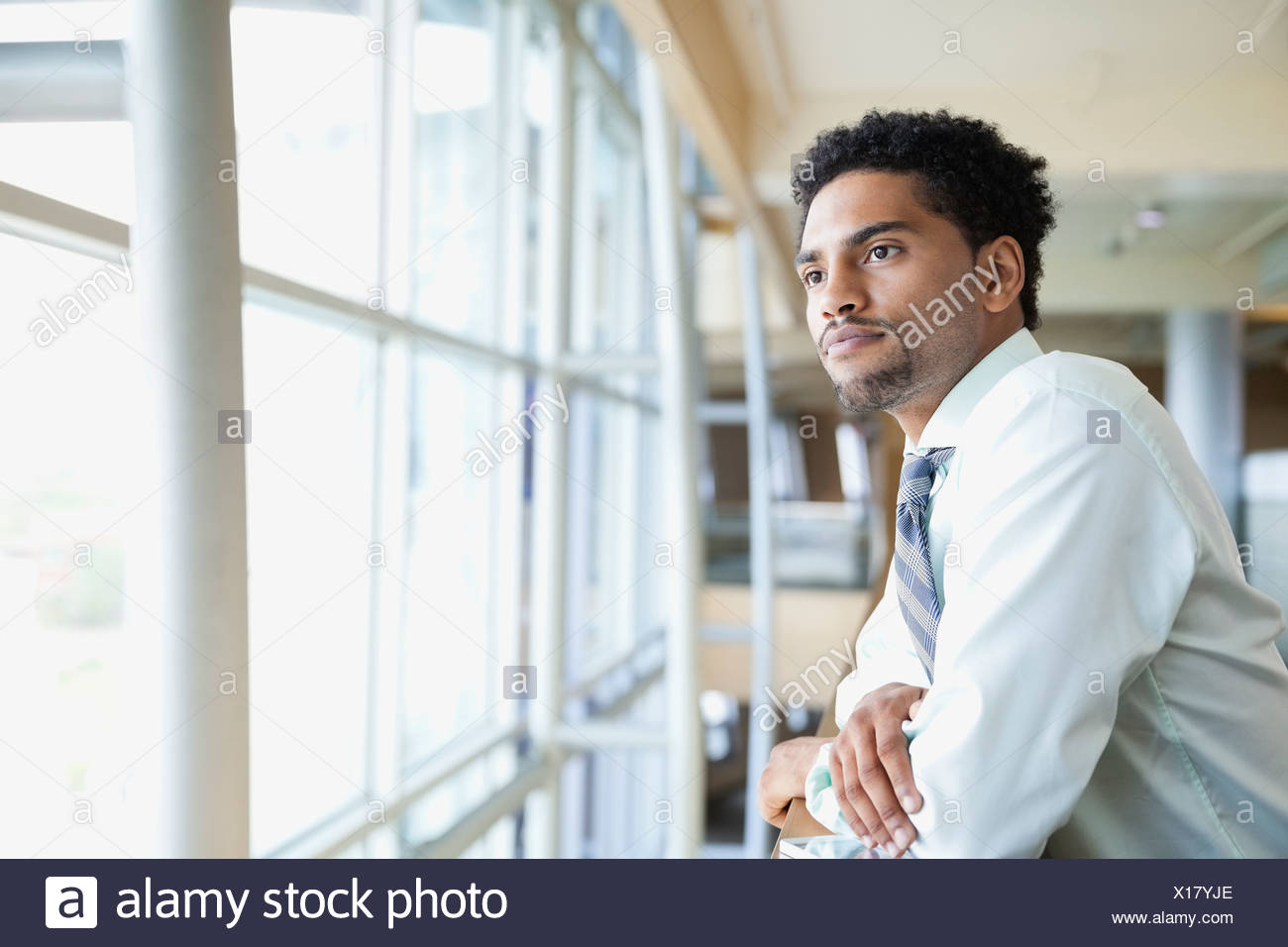 Side view of businessman leaning on railing - Stock Image