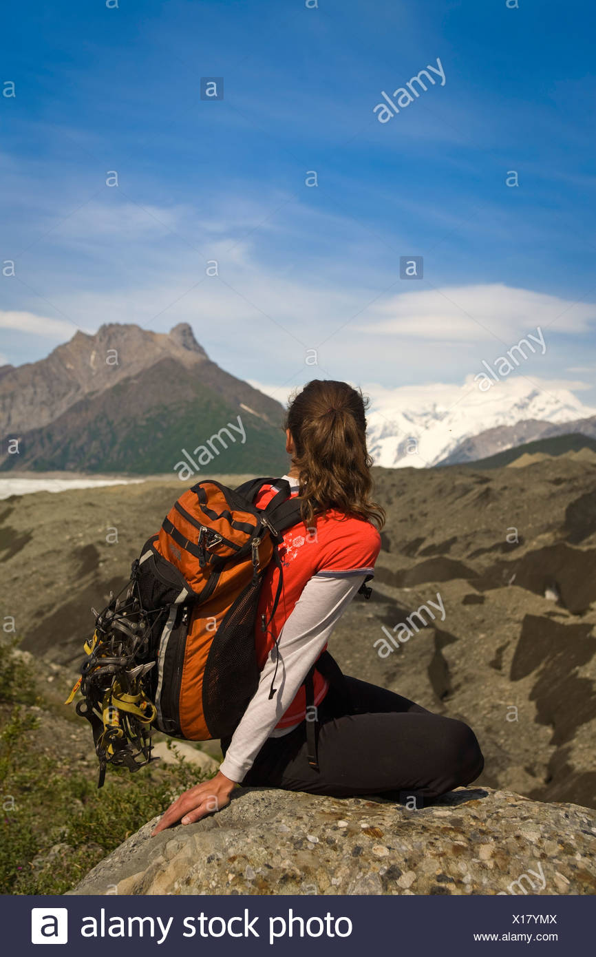 Woman looking out across the Root Glacier moraine near Kennicott in Wrangell-St.Elias National Park, Alaska - Stock Image