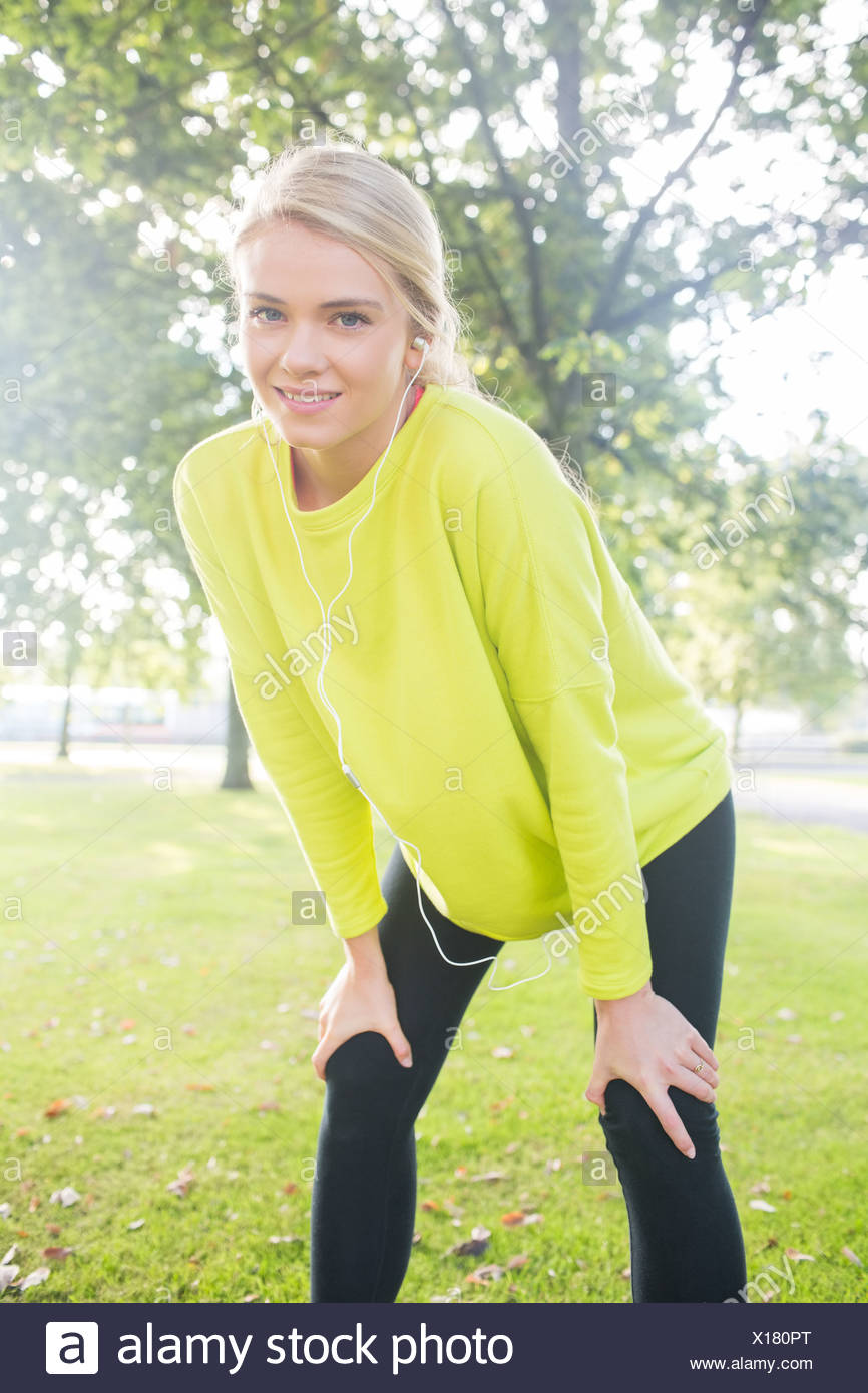 Active smiling blonde pausing after a run - Stock Image