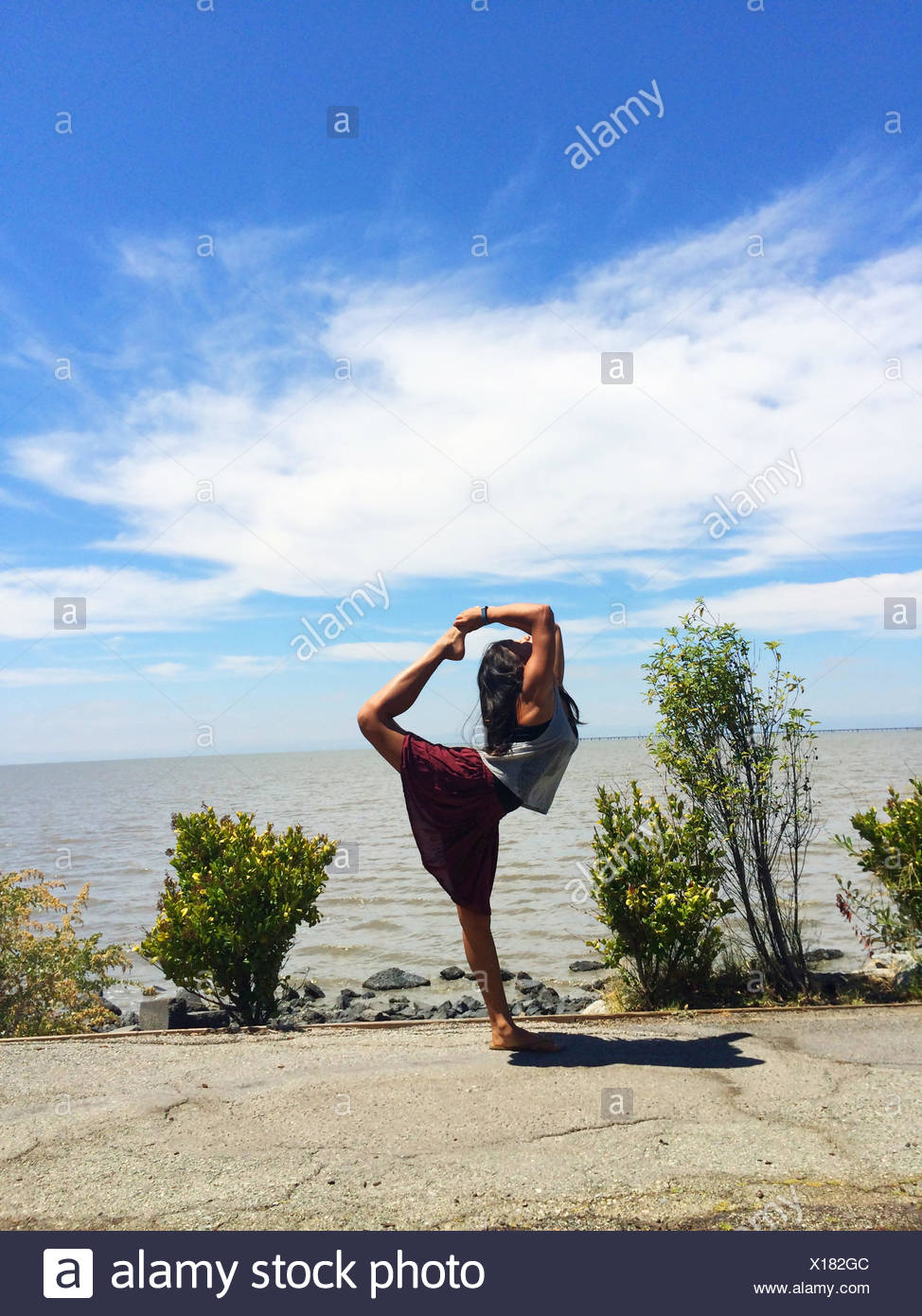 Girl doing standing bow pulling yoga pose on beach Stock Photo