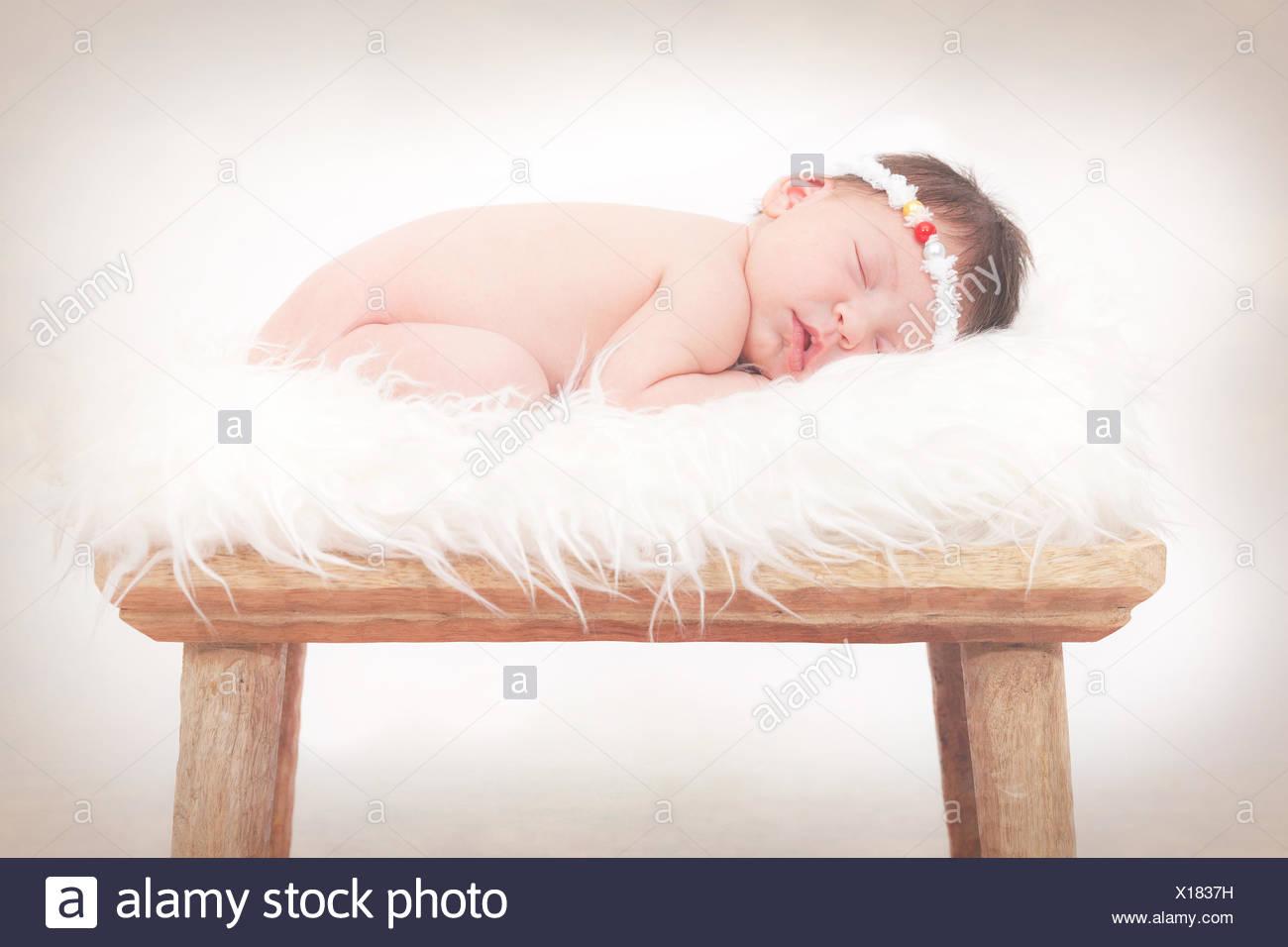 Portrait of a newborn baby girl sleeping on fluffy rug - Stock Image