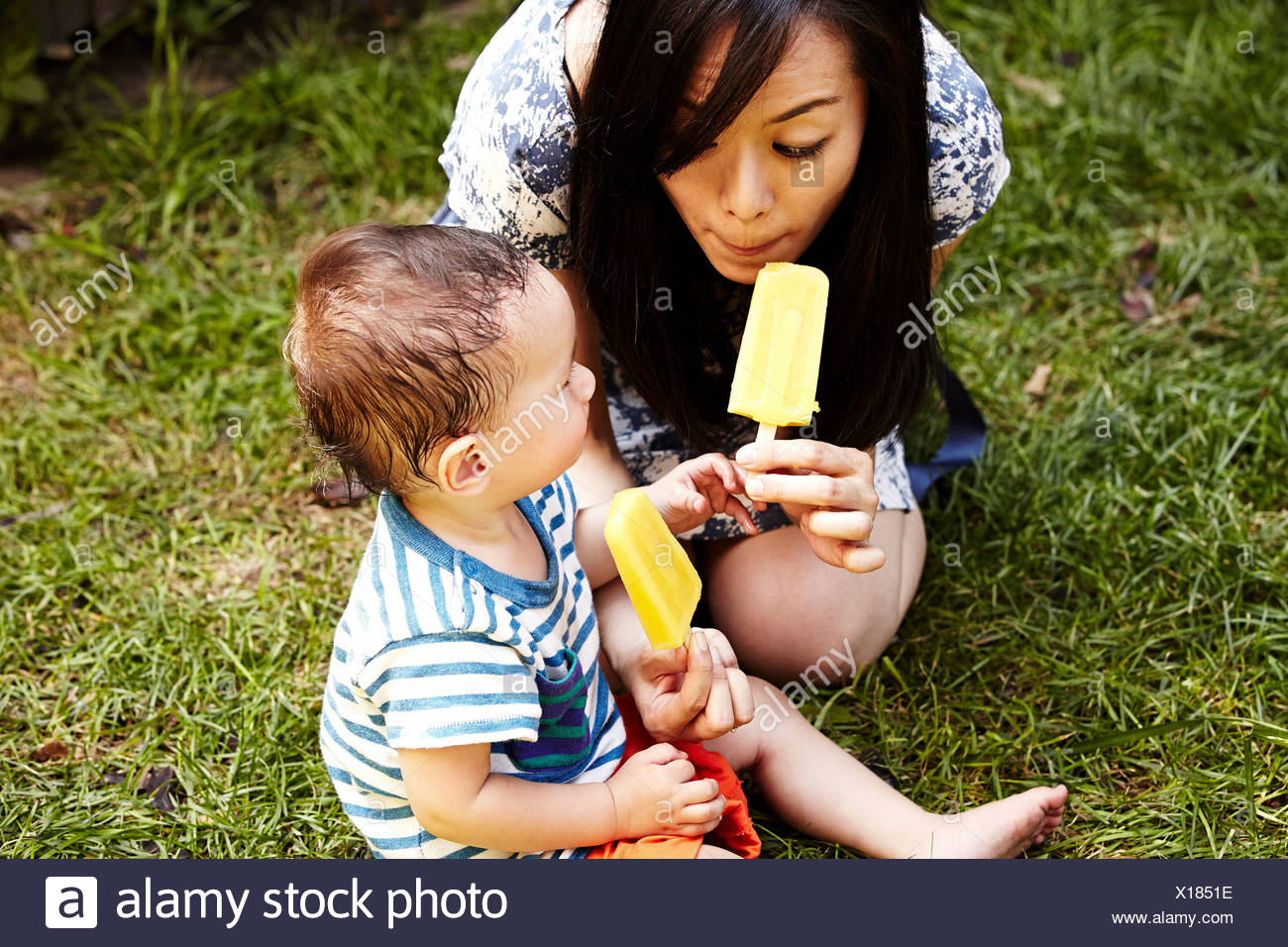 Mother and son sitting on grass eating ice lollies Stock Photo