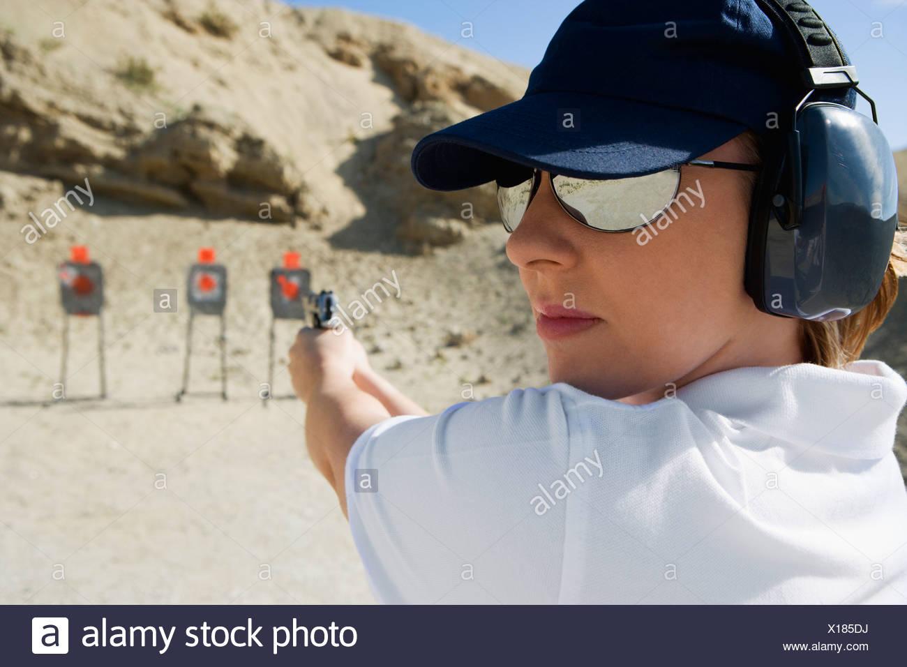 Woan aiming hand gun at firing range - Stock Image