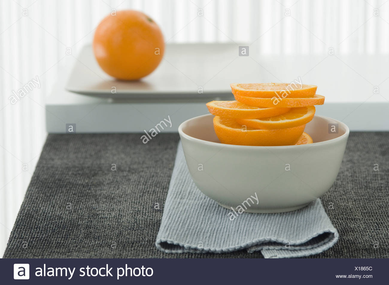 Slices of orange in bowl, close up - Stock Image