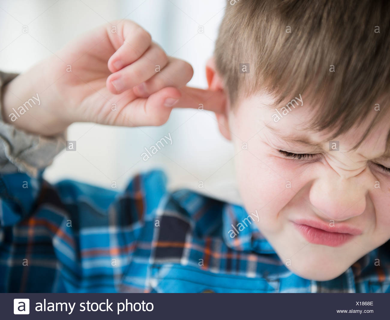 Portrait of boy (4-5) sticking fingers in his ears Stock Photo