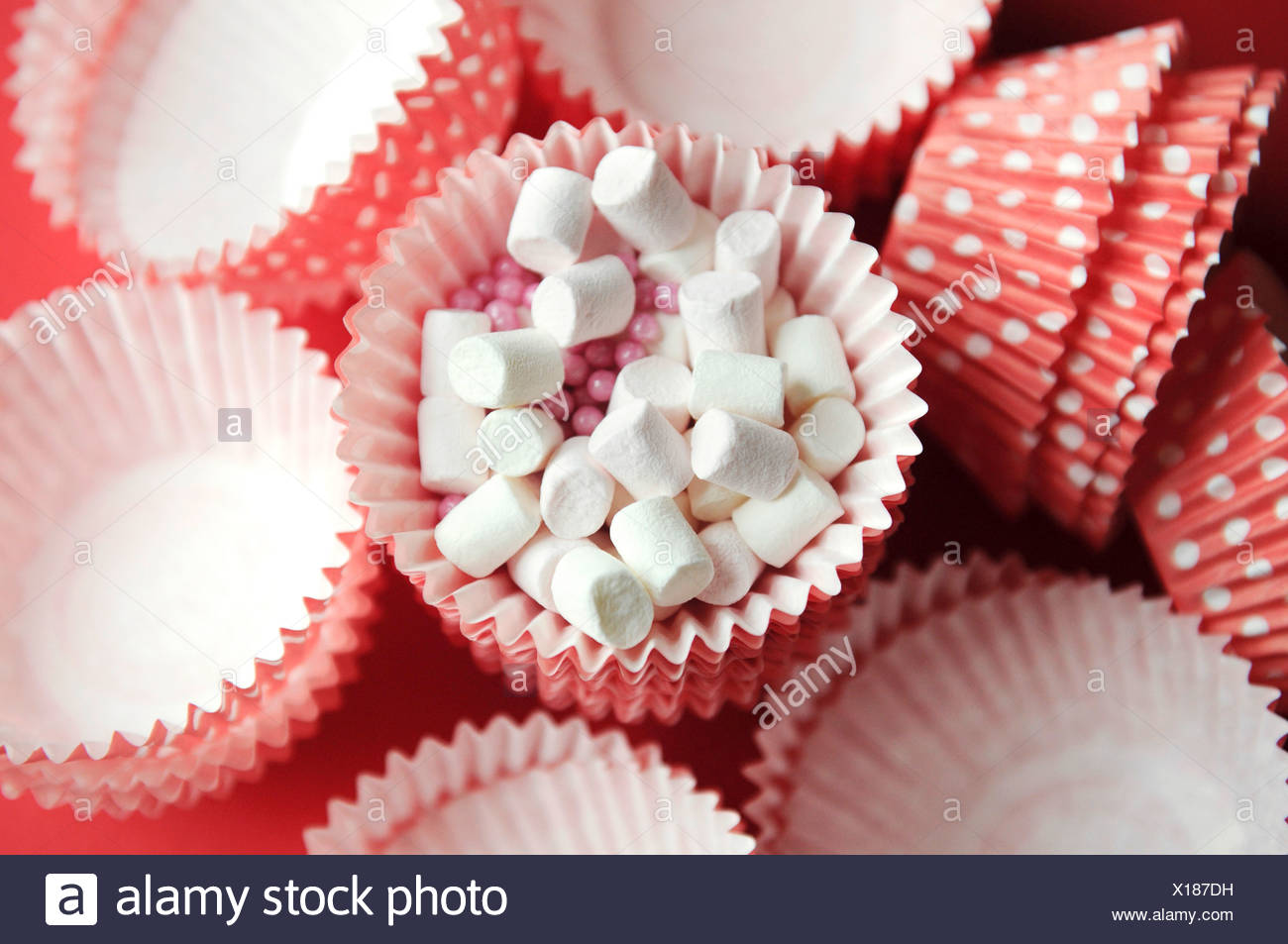 Pink Muffin cases with white dots and mini marshmallows - Stock Image