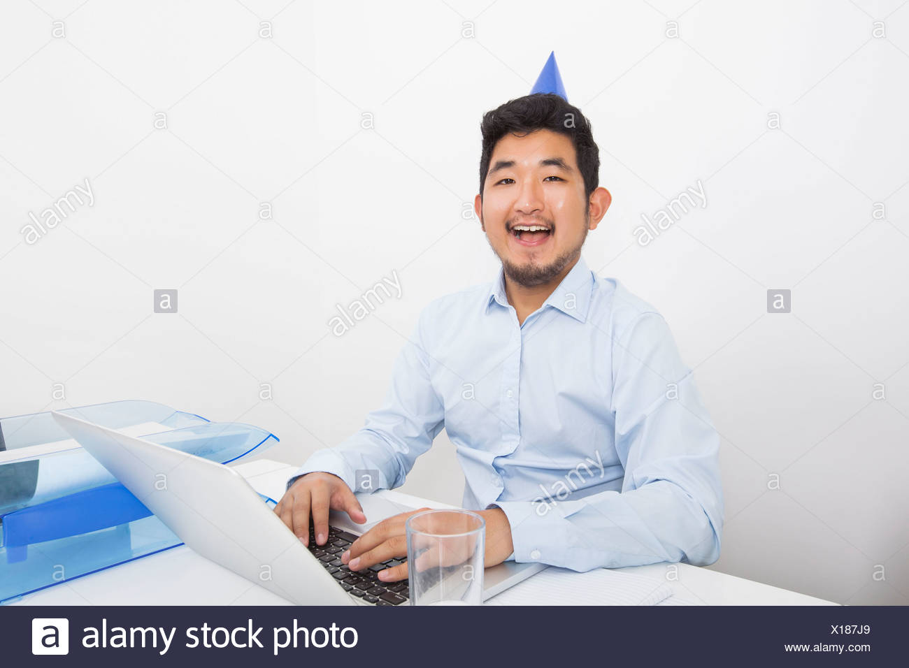 Portrait of happy businessman wearing party hat while working in office - Stock Image