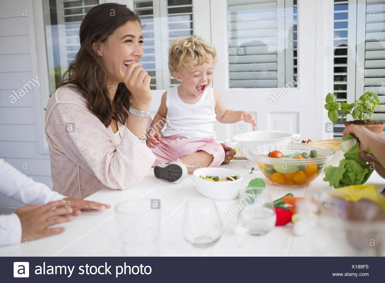 Happy family preparing food at home - Stock Image