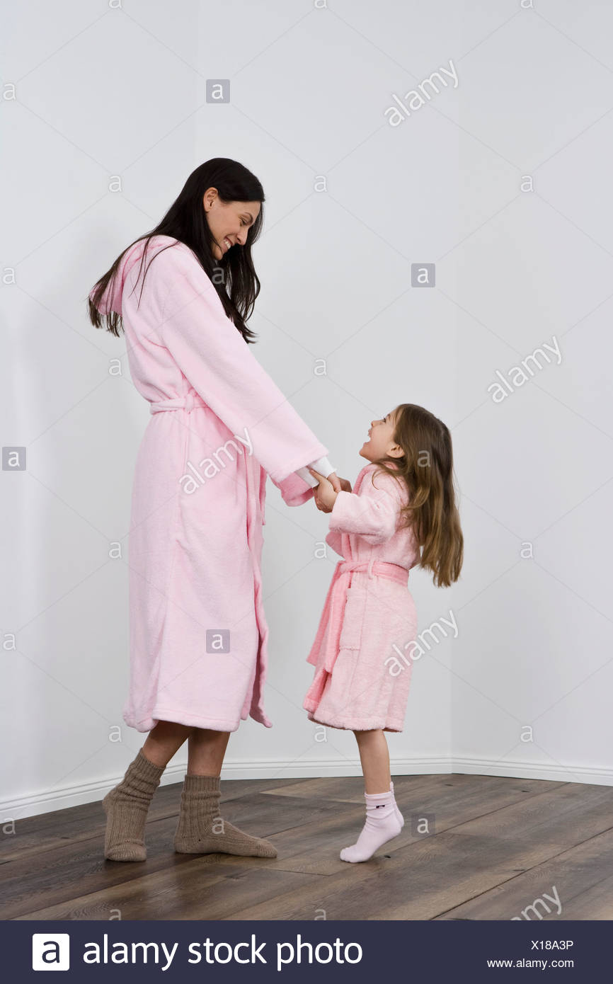 A daughter and mother in pink bathrobes holding hands - Stock Image