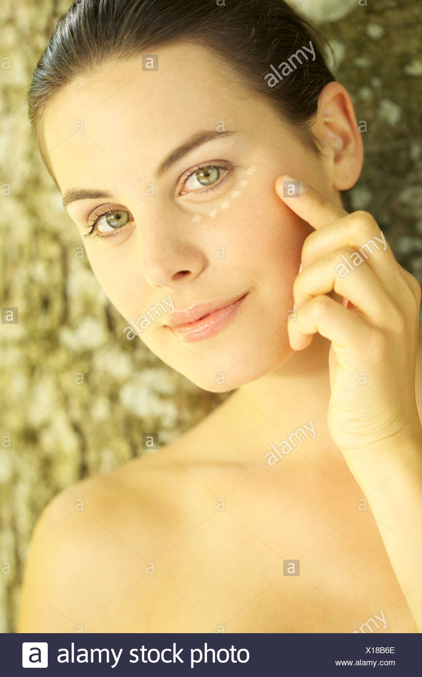 Portrait of young woman with foundation make-up dots under her eyes - Stock Image