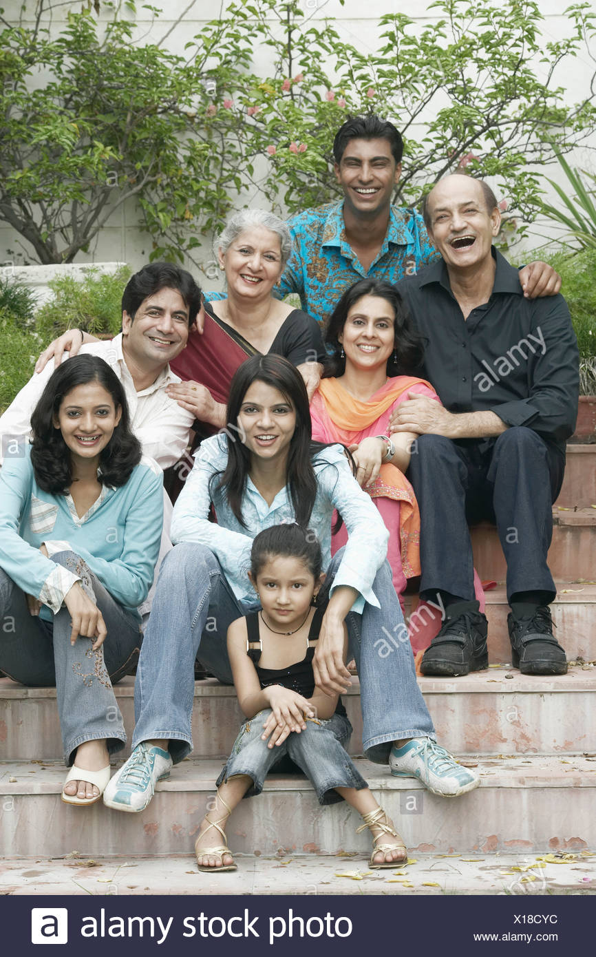 Portrait of a family sitting together on steps - Stock Image