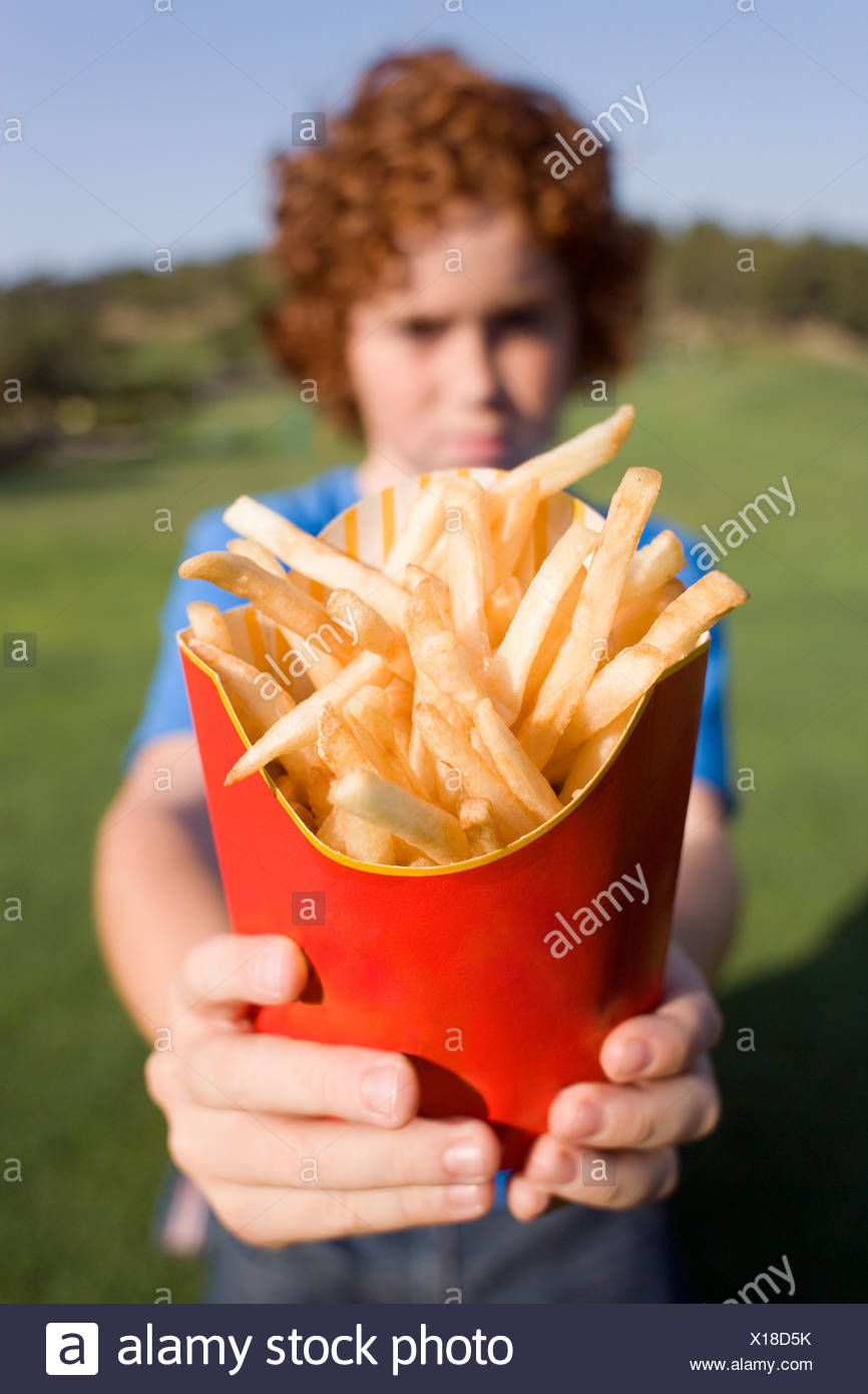 Boy holding chips. These are fried chipped potato portions. They are a popular fast food item. - Stock Image
