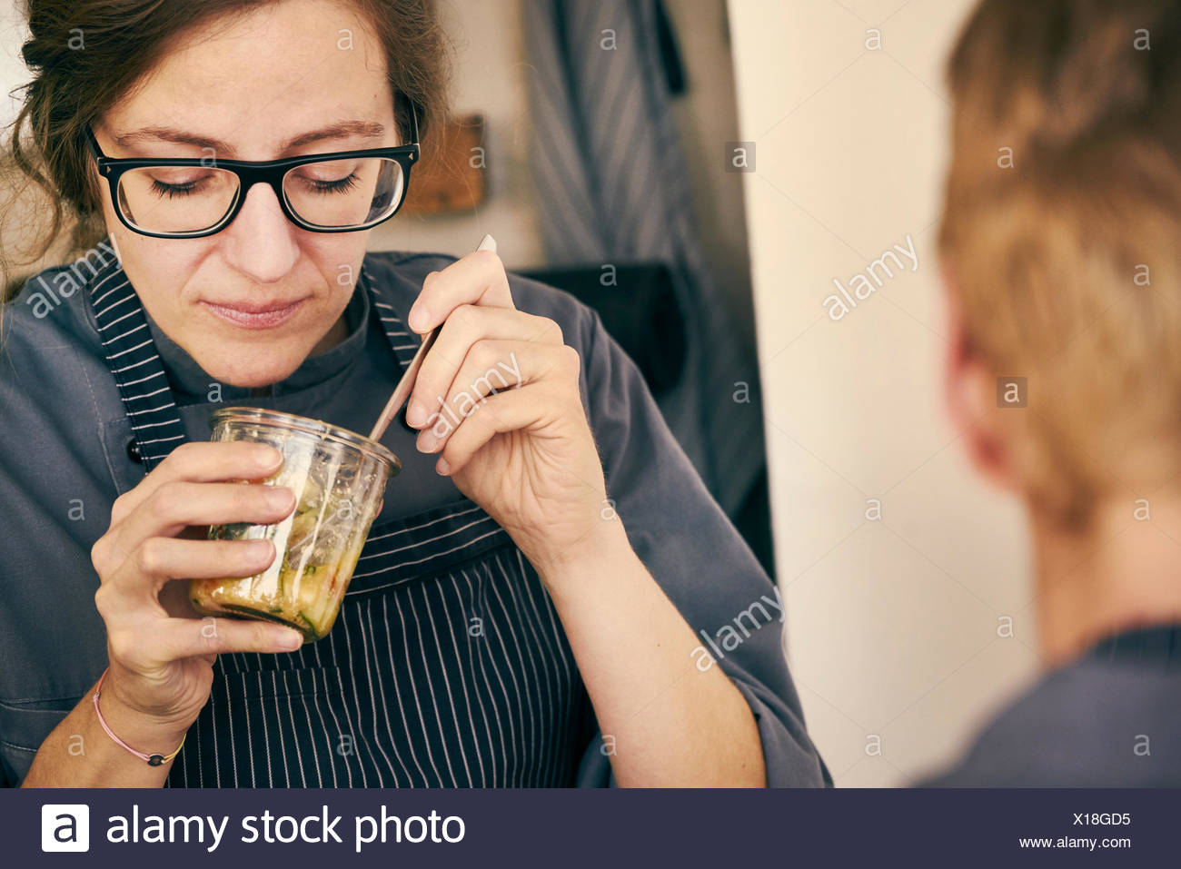 Chef eating food from glass jar - Stock Image