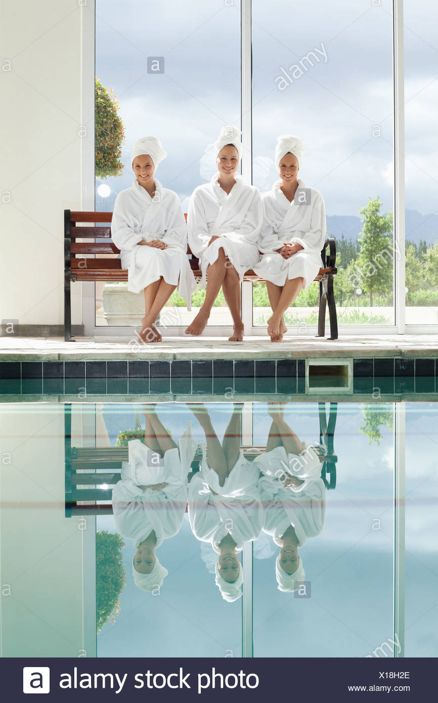Women in bathrobes talking on bench poolside at spa - Stock Image