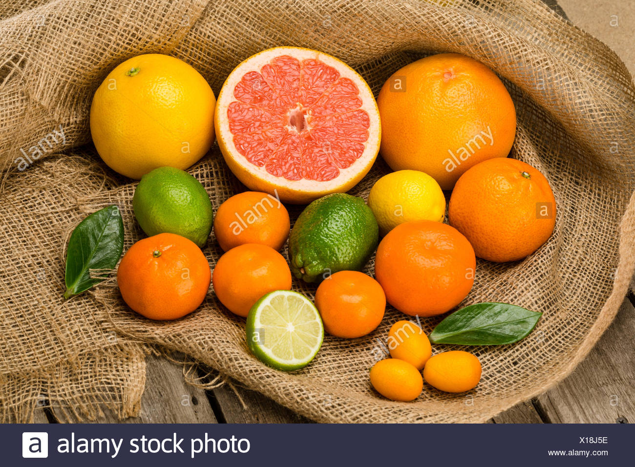 Close-up view of various whole and sliced fresh citrus fruits on sackcloth - Stock Image