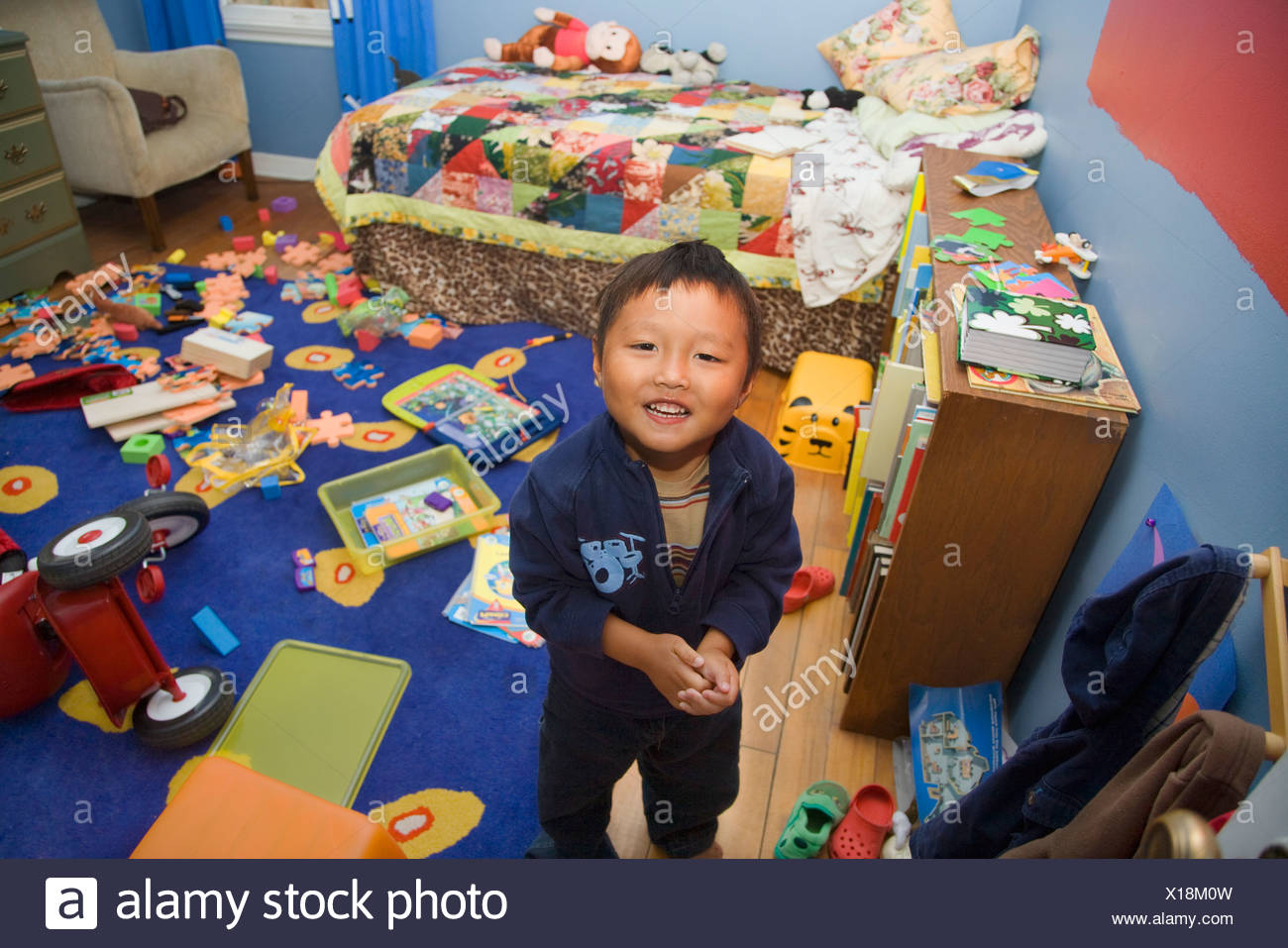 Asian boy in messy bedroom - Stock Image