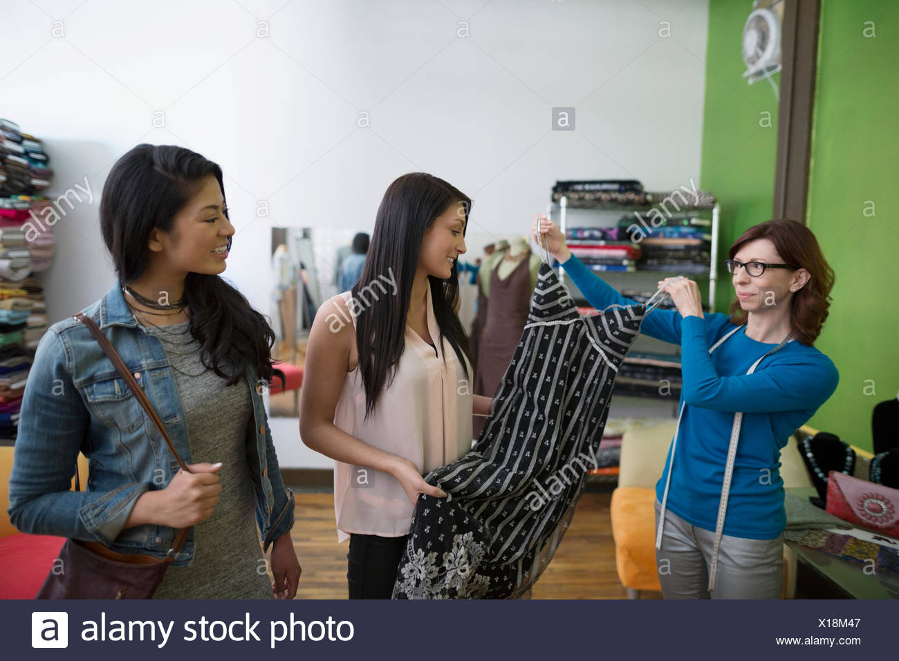Dressmaker showing women dress - Stock Image