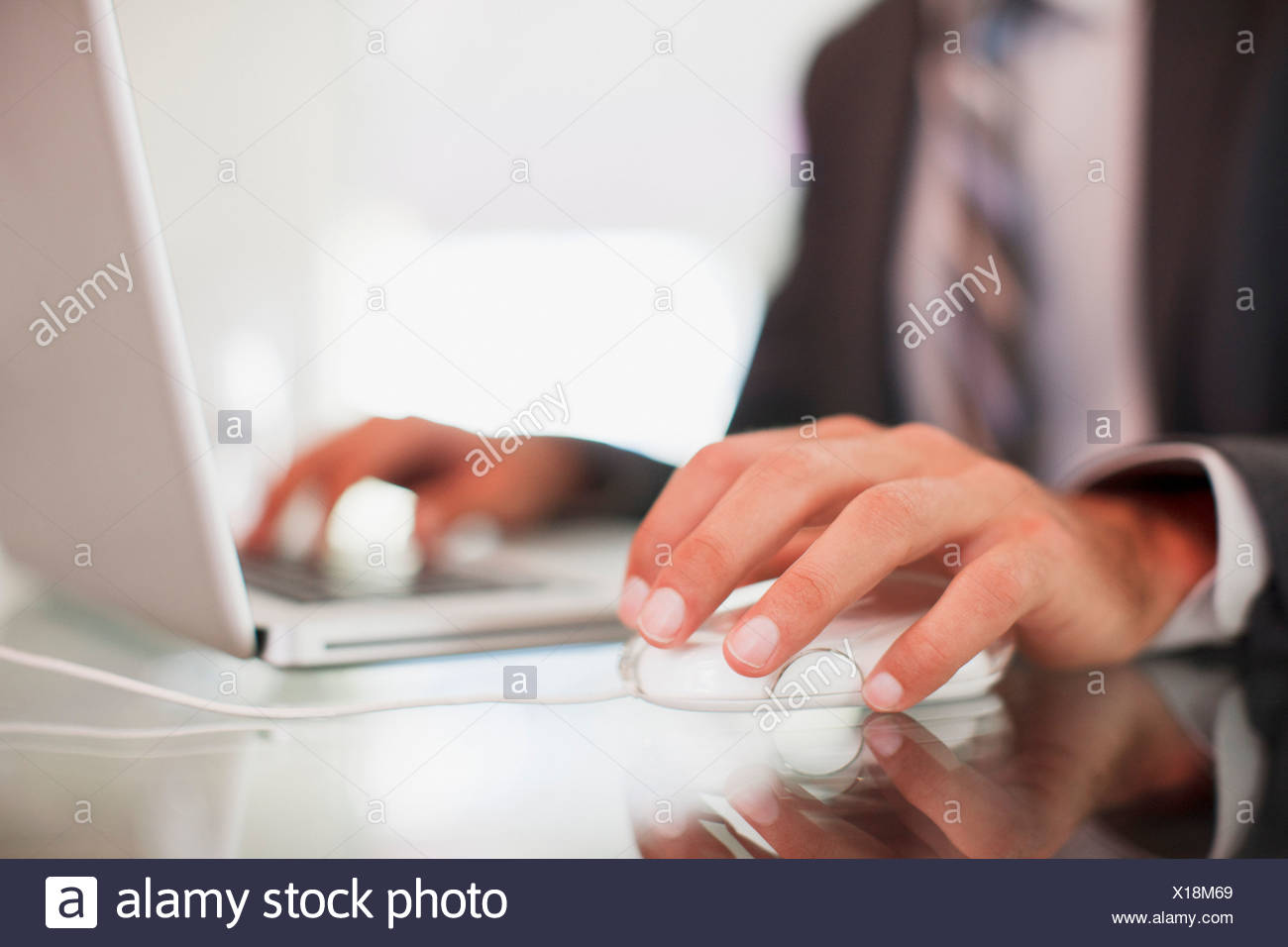 Businessman using computer mouse and typing on laptop - Stock Image