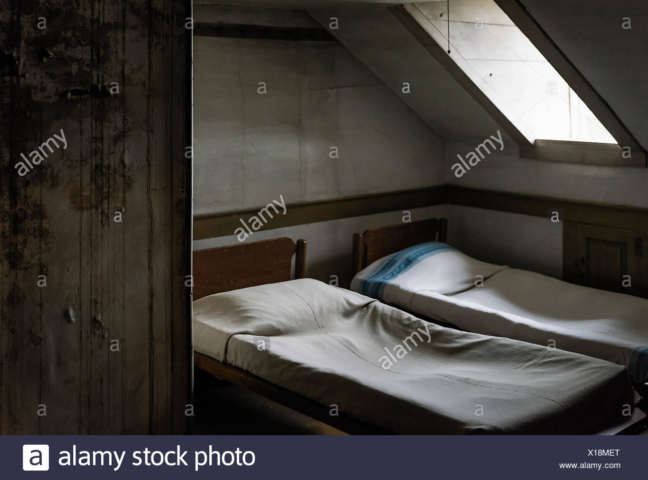 Austere bedroom with skylight. - Stock Image