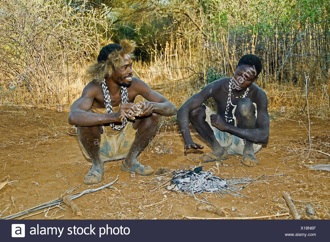 two Hadzabe bushmen at the fireplace, Tanzania, Lake Eyasi, Serengeti - Stock Image