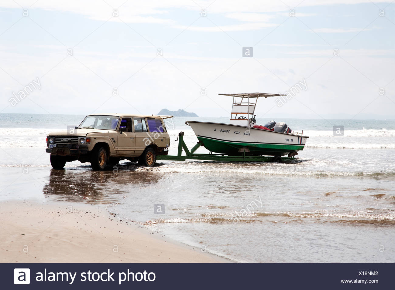 Car tugging boat out of water - Stock Image