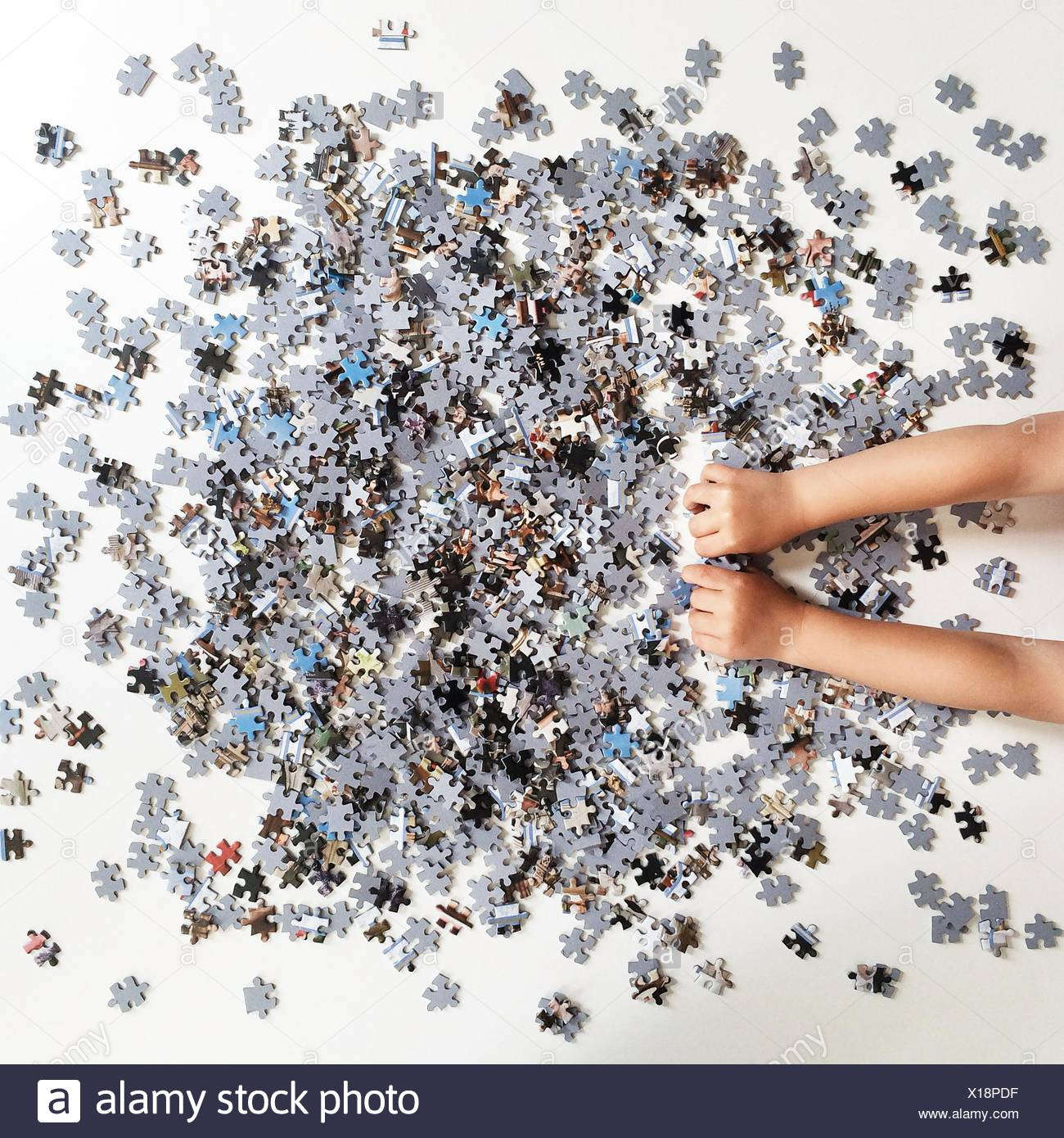 Human hands playing with jigsaw puzzle pieces - Stock Image