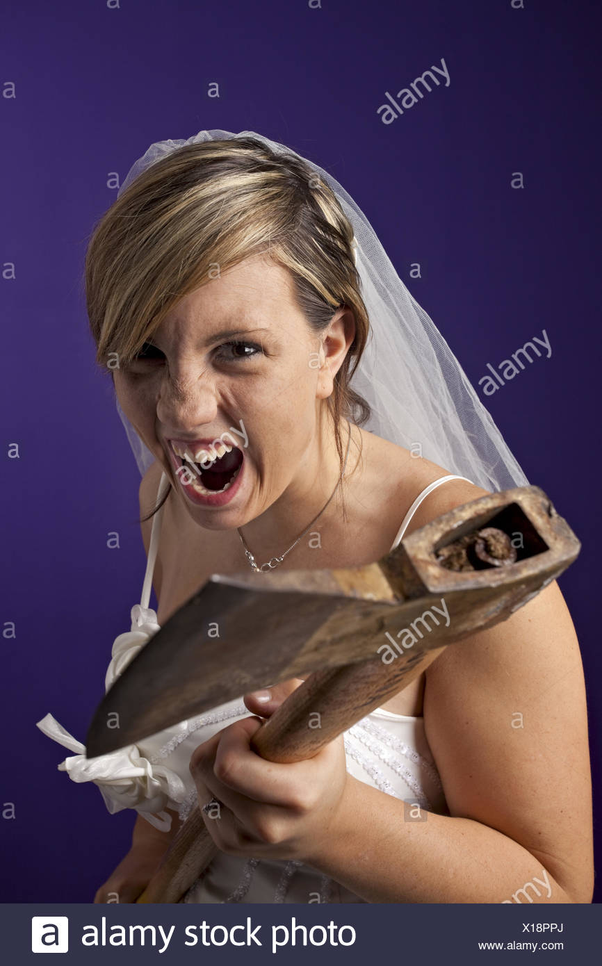 angry young bride with an axe on a dark blue background - Stock Image
