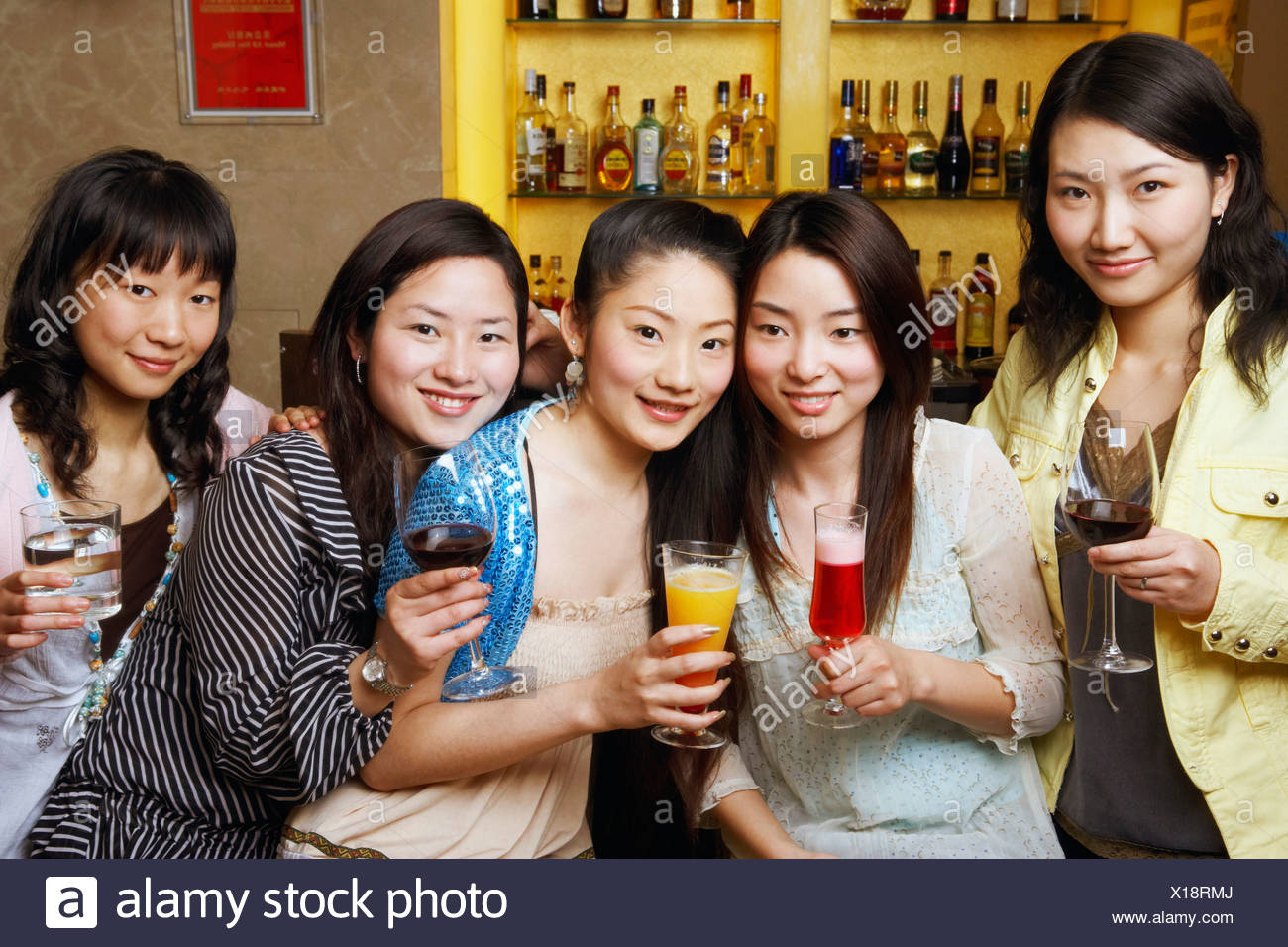 Portrait of three teenage girls and two young women holding drinks - Stock Image