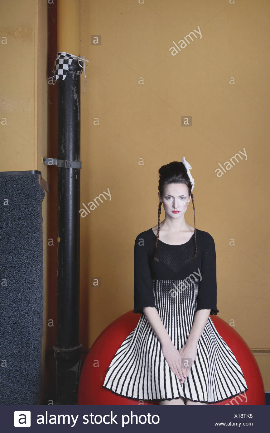Fashion photo, young woman in front of wall with old pipe, - Stock Image