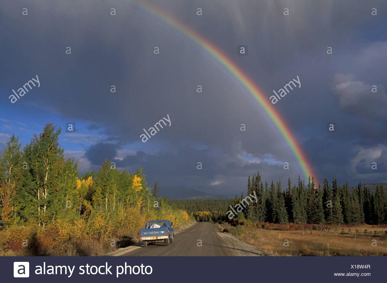 Tagish, Yukon, Canada, stormy sky, rainbow, rainbow, road, blue pickup, rain, low sun - Stock Image