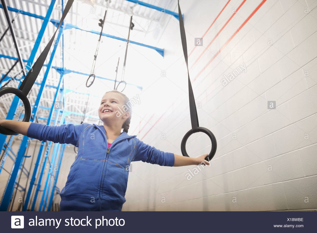 Girl holding onto gymnastic rings - Stock Image