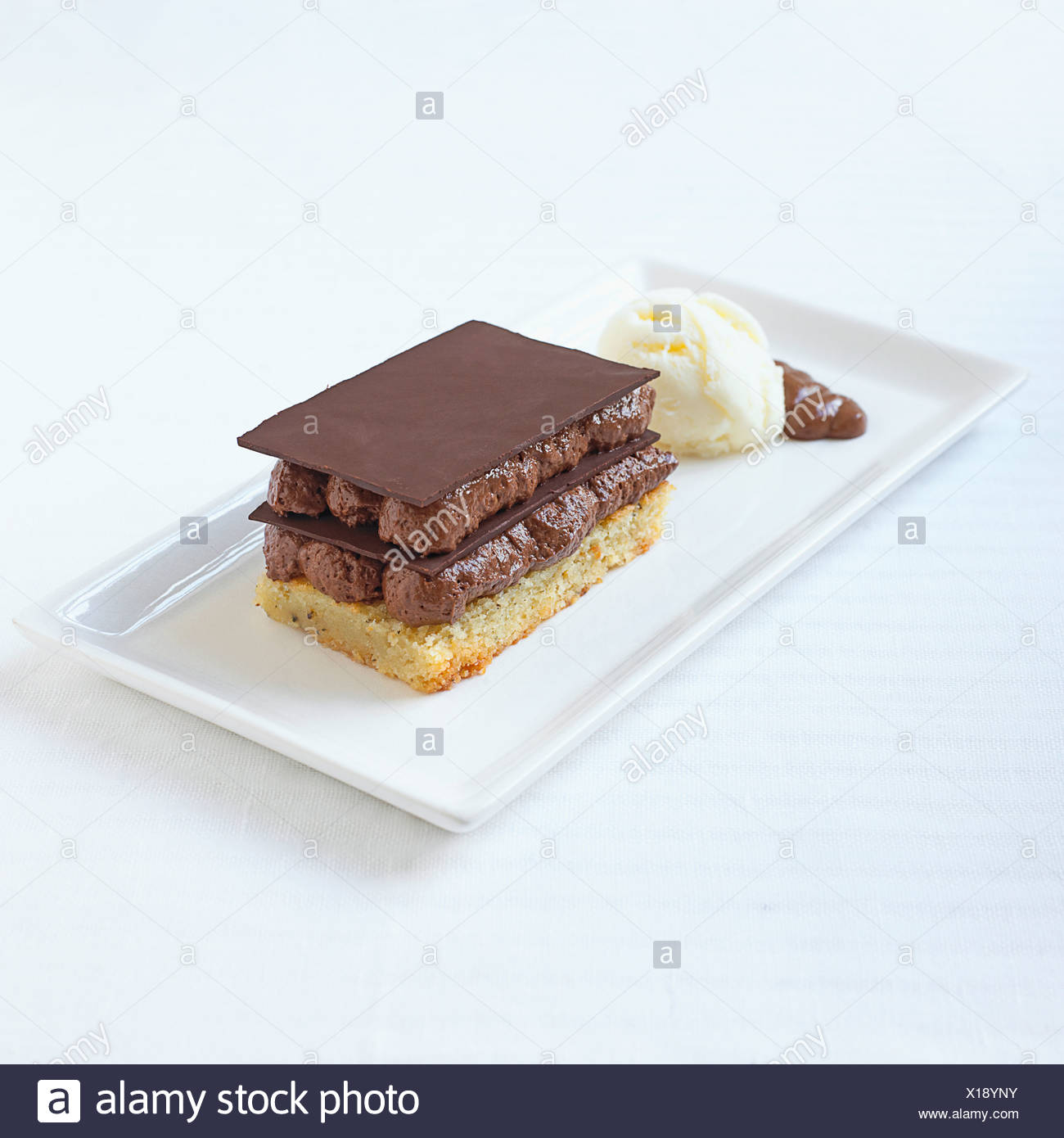 Dark chocolate mousse, green tea financier and ice cream desert on white rectangular plate, close-up - Stock Image