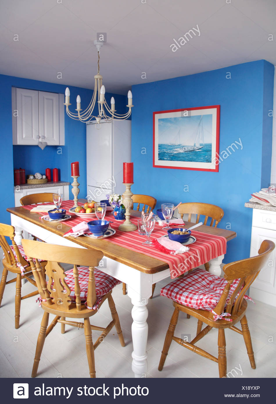 Red checked cushions on wooden chairs at painted table in ...