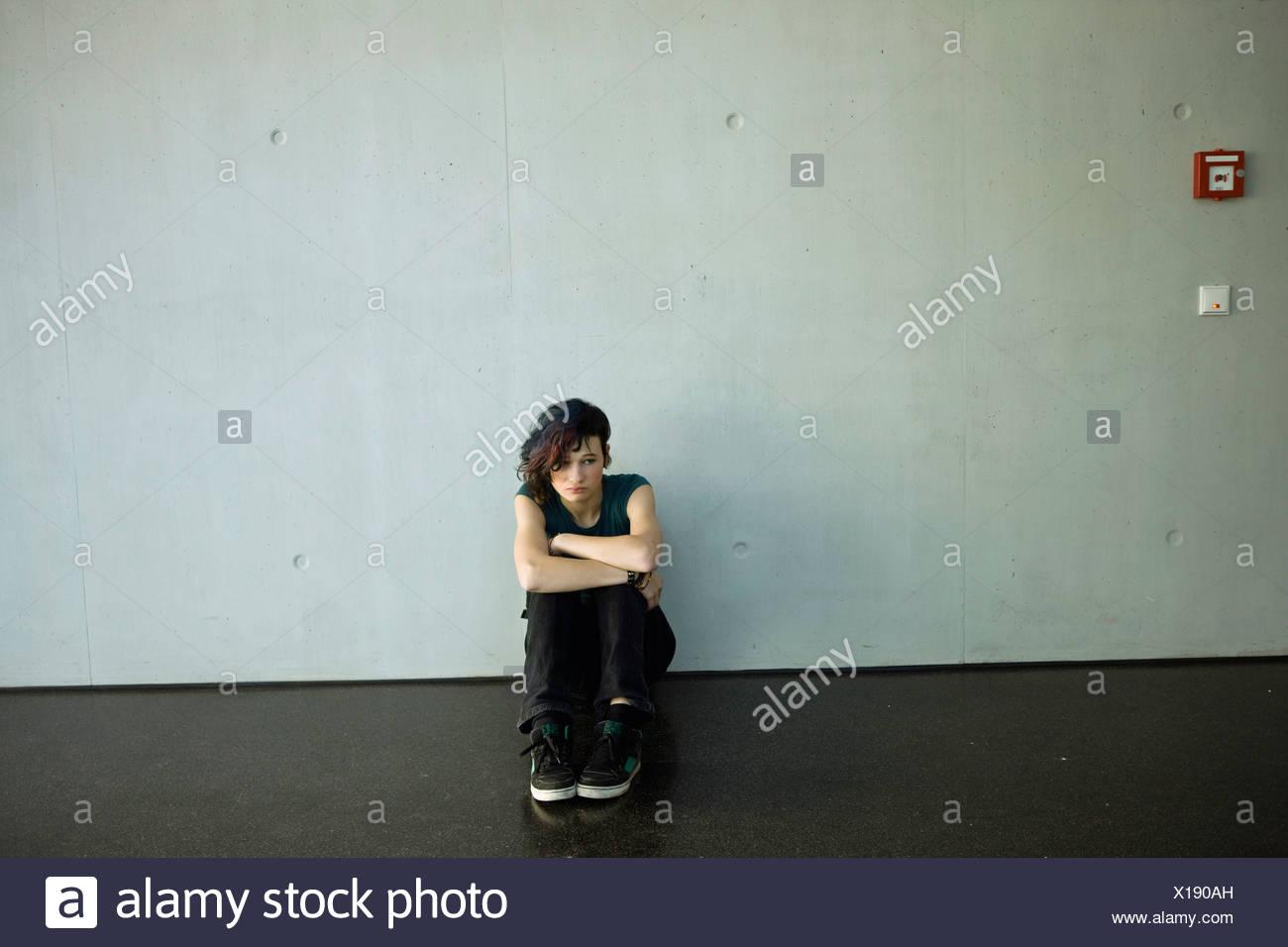 Sullen teenage girl sitting on floor barren room - Stock Image