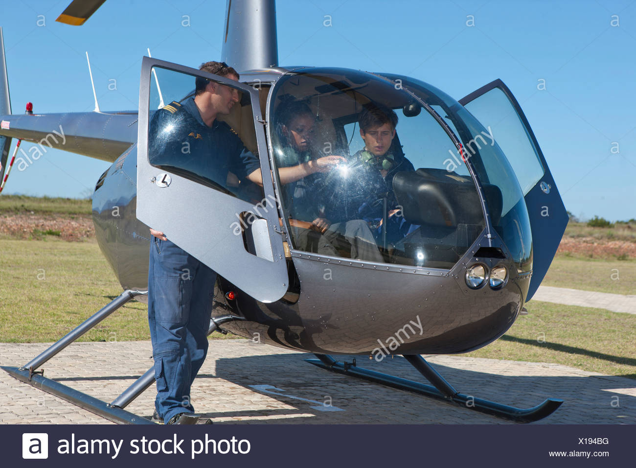 Flight instructor showing student pilots flight deck of helicopter - Stock Image