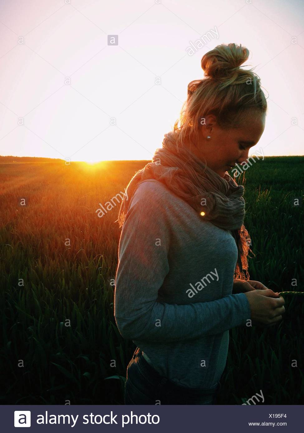 Side View Of Young Woman Standing On Field At Sunset - Stock Image