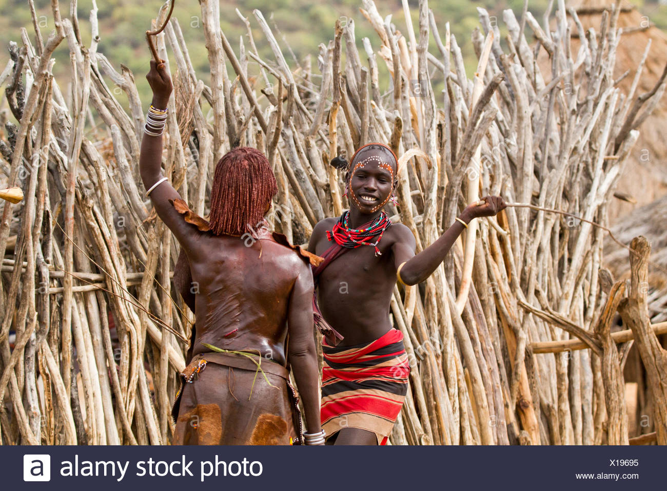 Man with reed whip ready to flog a female member at the Hamar tribe's  'Jumping of the Bull' ceremony. Omo Valley Ethiopia - Stock Image