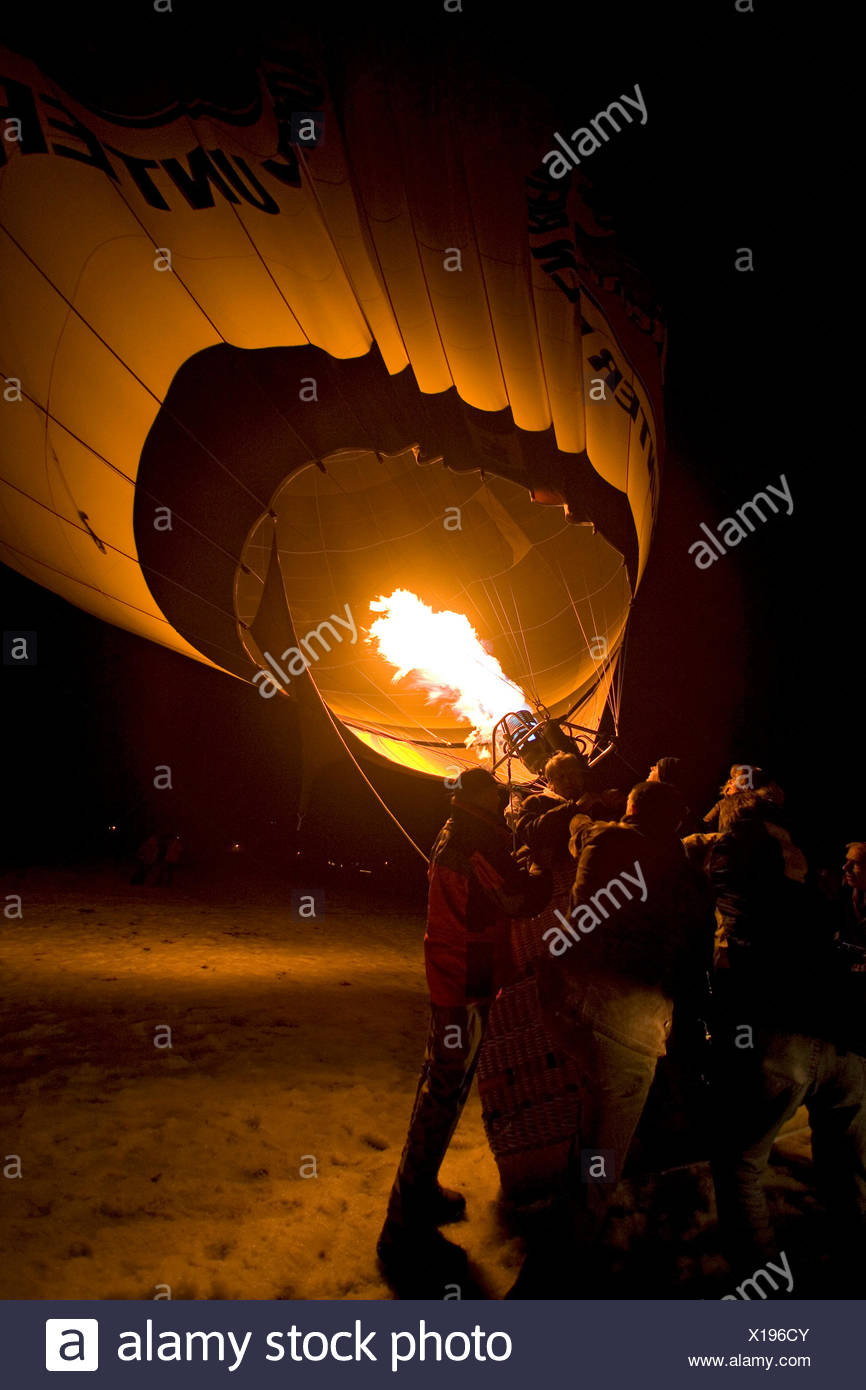 hot-air balloon being held on a snow foeld at night by several persons while being fired and erecting, Germany, Bavaria, Allgaeu, Oberstdorf - Stock Image