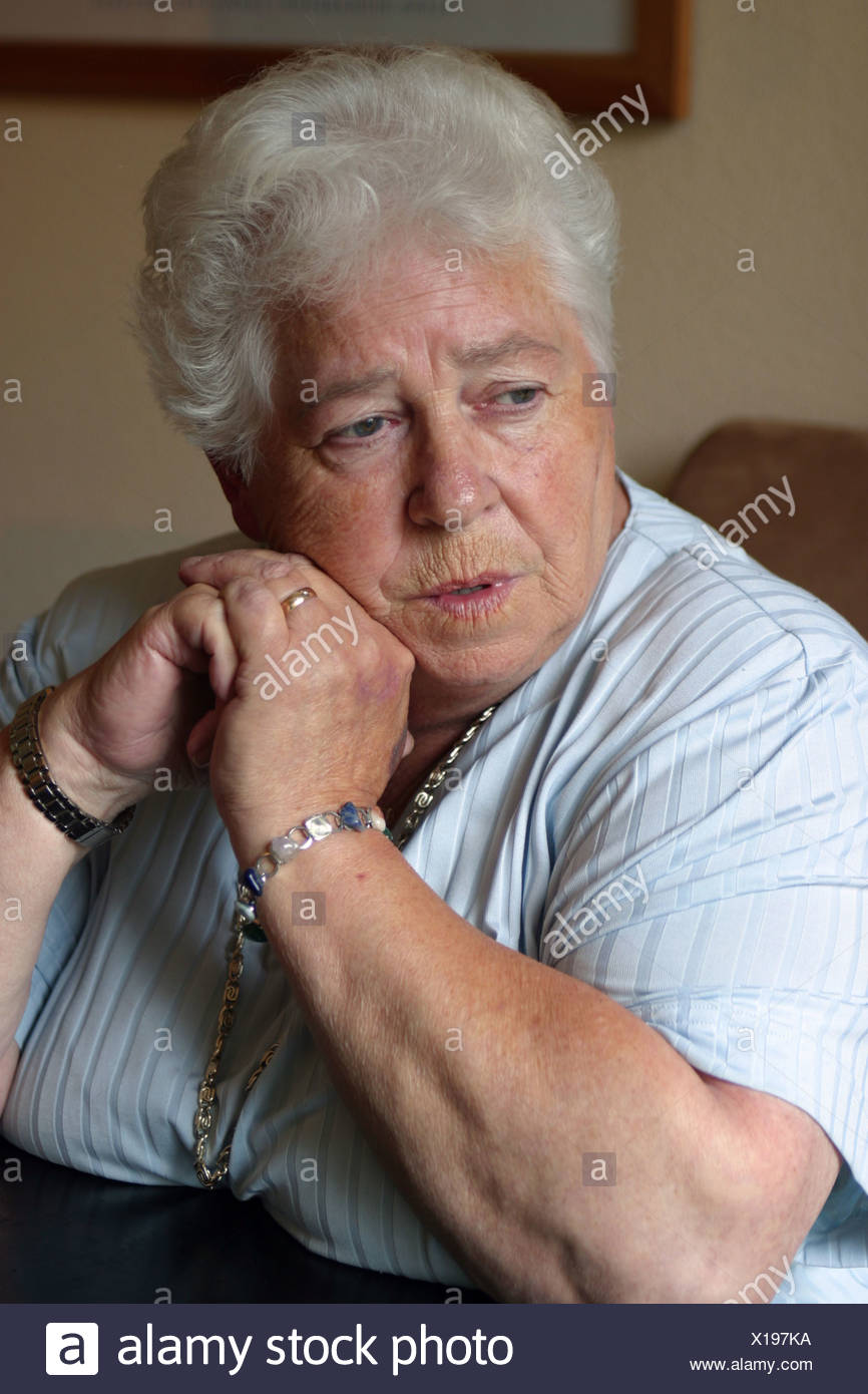 Elderly woman looking upset or frustrated or mature recall past occurrences or recollecting reminiscences - Stock Image