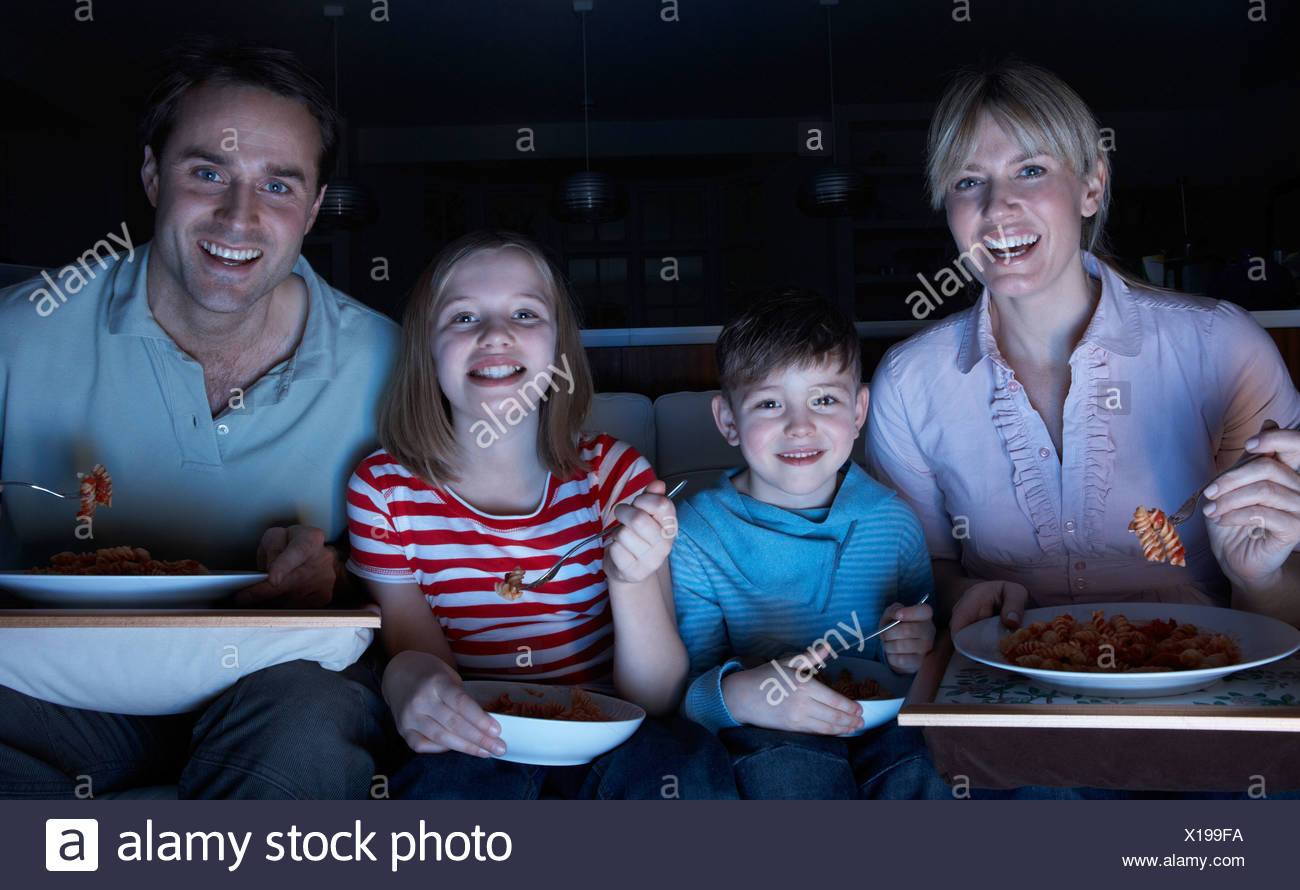 Family Enjoying Meal Whilst Watching TV - Stock Image