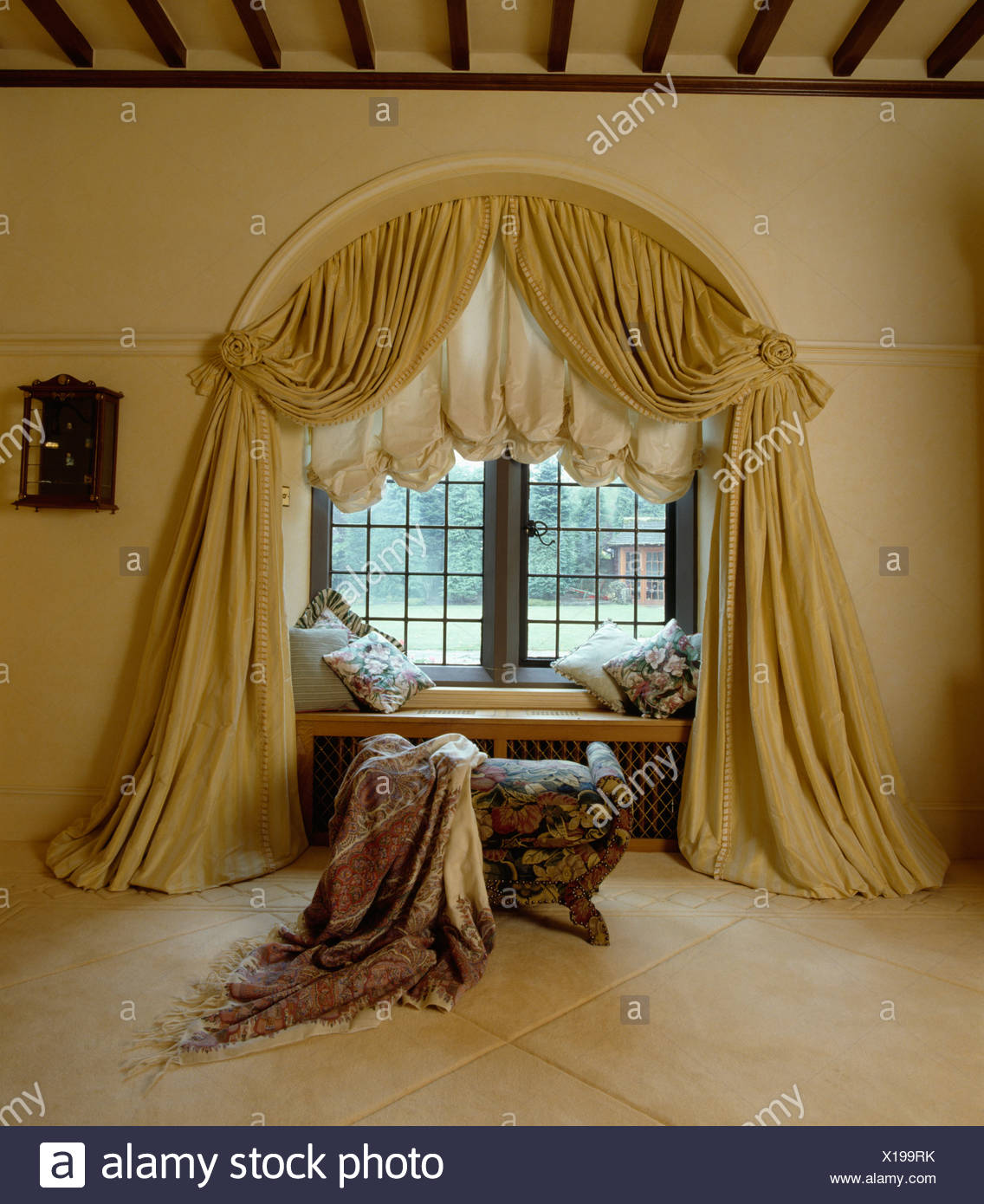Cream Draped Curtains And Festoon Blind On Arched Window In Bedroom With Patterned Throw Onstool Front Of