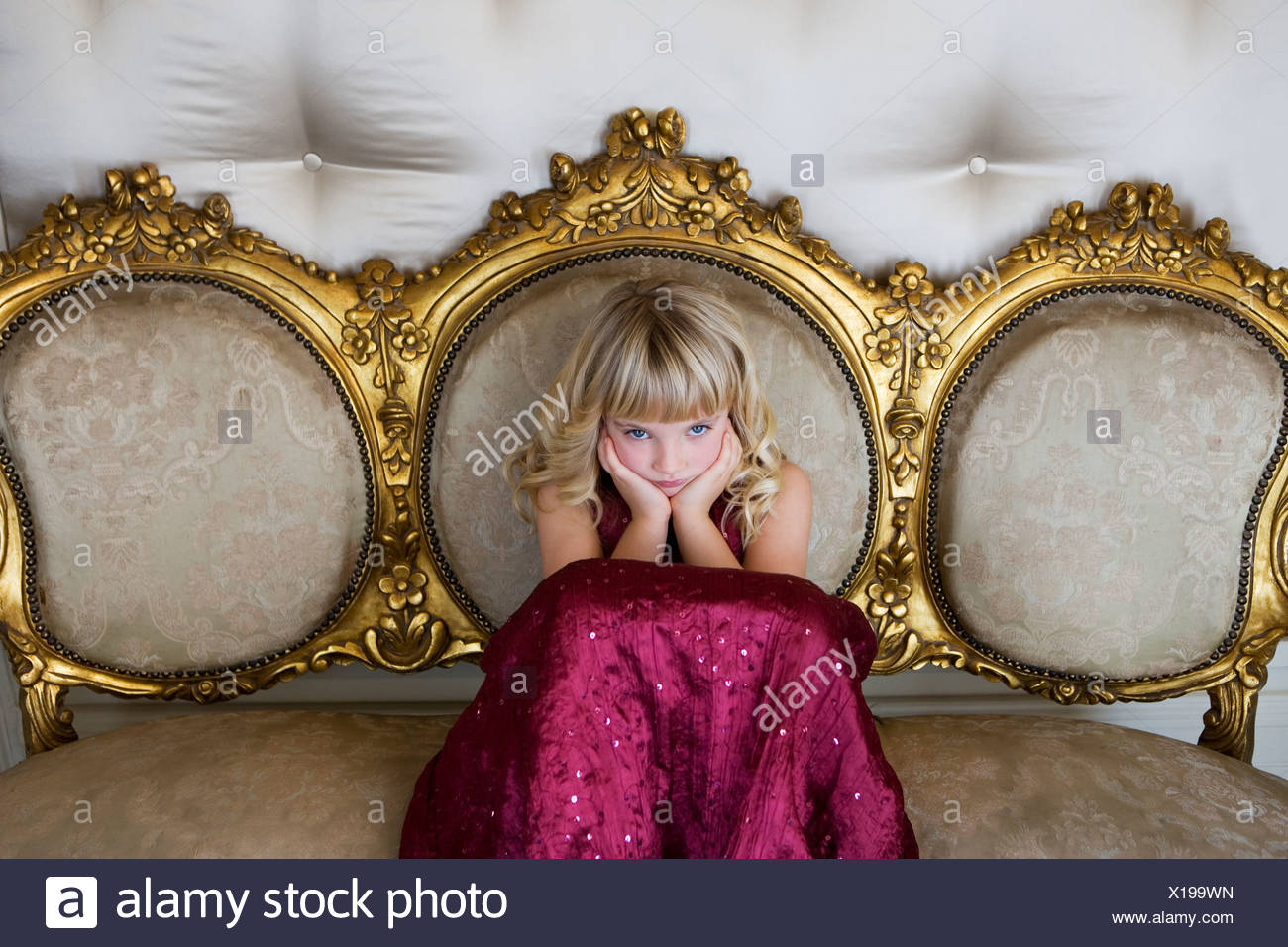 Young girl in a party dress sulking - Stock Image