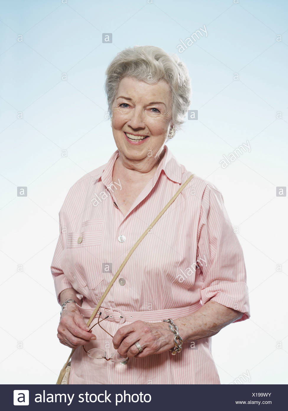 Profile of smiling senior woman holding her glasses - Stock Image