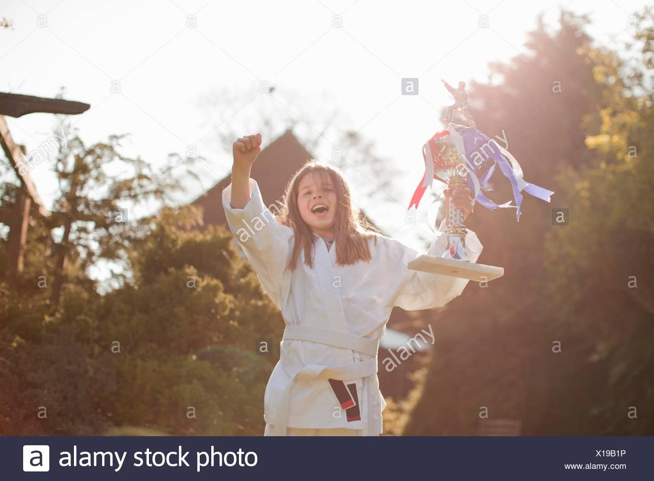 Portrait of joyous girl celebrating trophy in garden - Stock Image