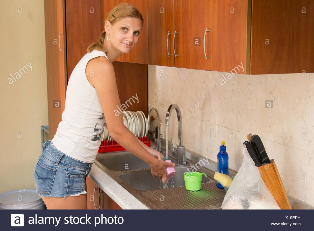 Young girl housewife washing dishes in the kitchen. - Stock Image
