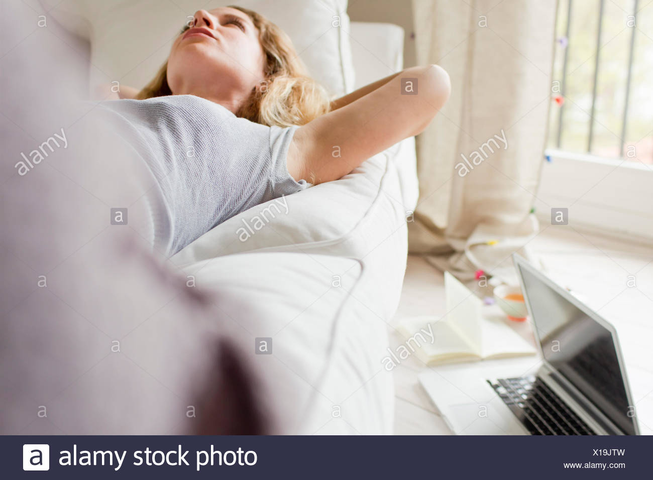 Woman lying on sofa day-dreaming - Stock Image