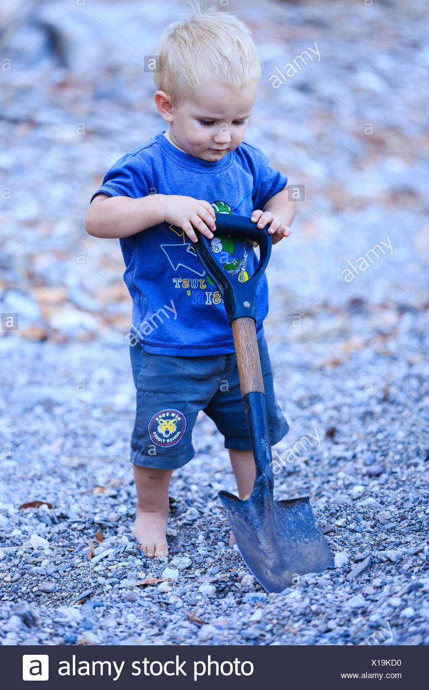 Little boy playing with spade in the gravel, Damaraland, Kunene Region, Namibia - Stock Image