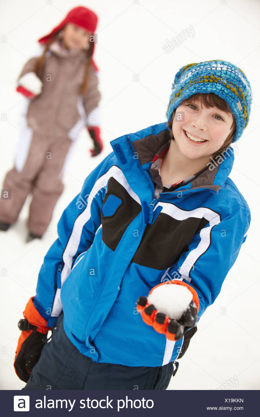 Two Young Children Having Snowball Fight Wearing Woolly Hats - Stock Image